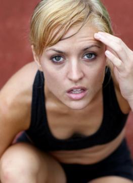 Junge Frau beim Sport - mit der linken Hand fasst sie sich an den Kopf