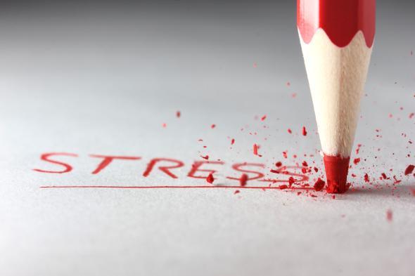 """Mit einem Buntstift schreibt jemand das Wort """"Stress"""" während die Spitze des Stift bricht."""