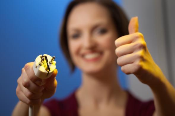 Eine Frau hält einen Stromstecker in der rechten Hand, mit der linken Hand signalisiert sie: Daumen hoch.