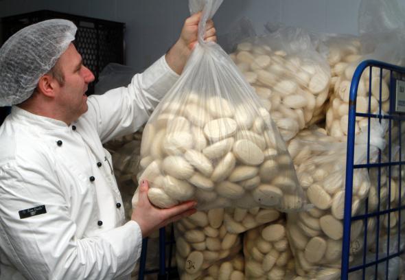 Bäckergeselle lagert schockgefrorene industriell hergestellte Teiglinge ein.