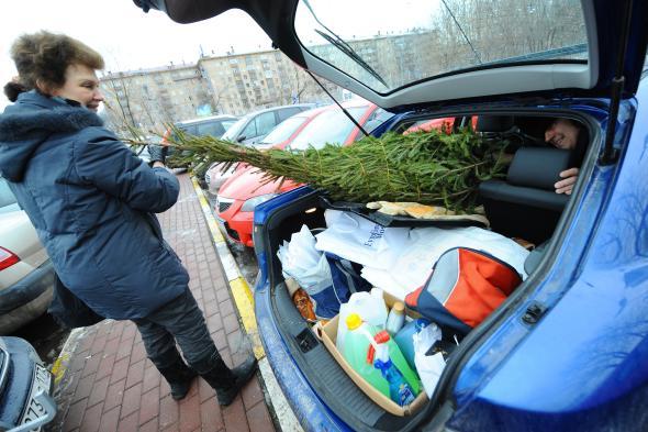 Ehepaar versucht den Weihnachtsbaum innen im Auto zu verstauen