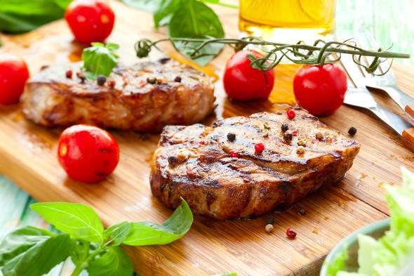 Zwei Steaks mit Tomaten auf einem Holztablett