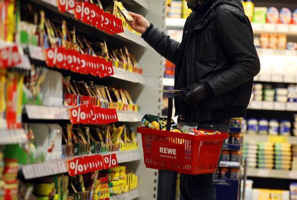 Junger Mann steht vor einem Regal mit Tütensuppen im Supermarkt.