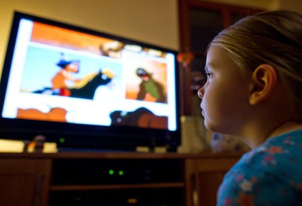 5 jähriges Mädchen sitzt vor dem Fernseher und schaut sich eine Kindersendung an.