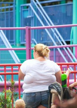 Junge Frau mit starkem Übergewicht (Adipositas) in einem Park