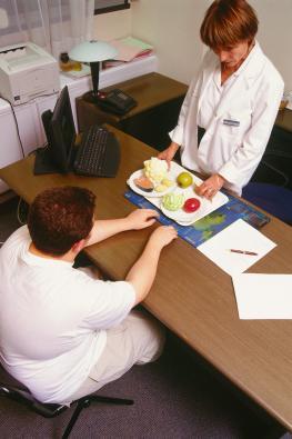 Übergewichtiger Junge wird bei einer Ernährungsberaterin über gesunde Ernährung aufgeklärt