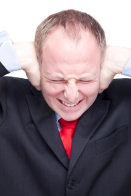 Ein Mann hält sich beide Ohren zu