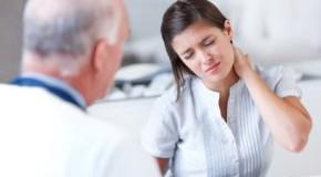 Untersuchung beim Arzt - die junge Frau hat starke Nackenschmerzen