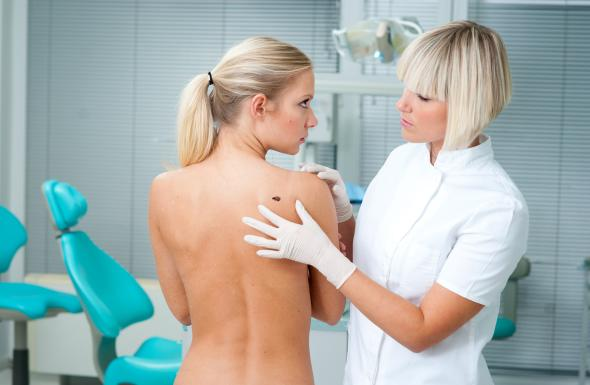 Ärztin untersucht eine junge Frau auf Veränderungen der Haut.