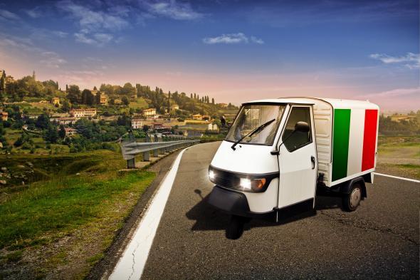 Kleiner Lieferwagen mit italienischer Flagge vor einem wunderschönen Panorama.