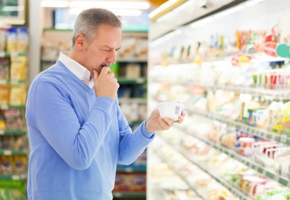 Nachdenklicher Älterer Mann steht am Milchprodukte-Regal im Supermarkt.