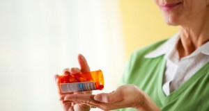 Seniorin nimmt Tabletten ein