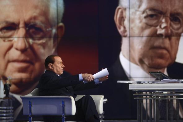 """Silvio Berlusconi in der TV-Sendung """"Porta a porta"""", im Hintergrund auf der Videoleinwand ist Ministerpräsident Mario Monti zusehen."""