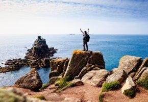 Wanderer steht auf einer Felsenklippe in Cornwall