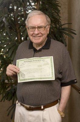 Warren Buffet mit einer Aktie in der Hand