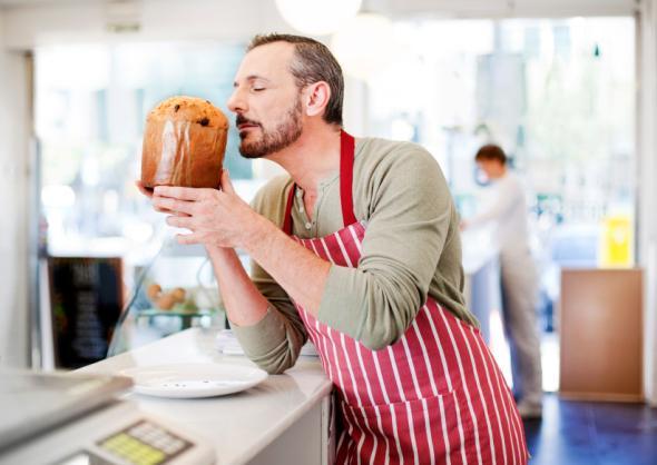 Bäcker riecht am frisch gebackenen Panettone
