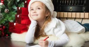 Kleines Mädchen schreibt einen Wunschzettel an den Weihnachtsmann.