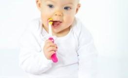 Zahnpflege beim Säugling - Baby putzt den Gaumen und Milchzähne mit einer Zahnbürste