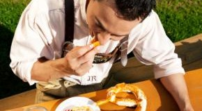 Junger Mann ißt eine Brezel